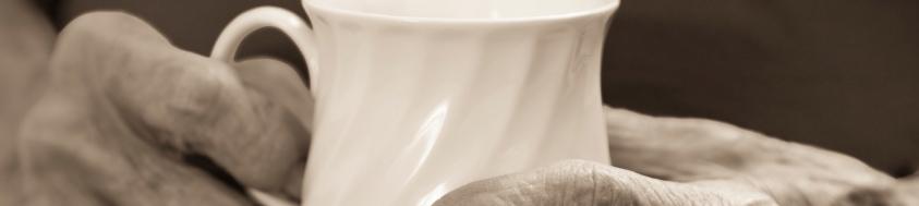 senior woman arthritis hands holding white mug